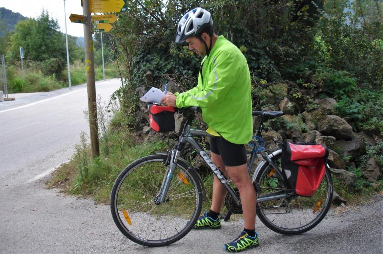 Cyclist reading road book notes